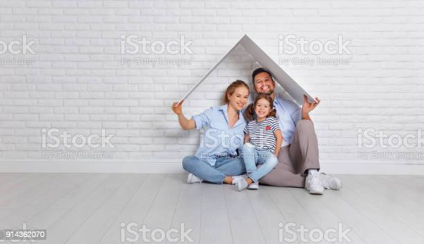 concept housing a young family. Mother father and child in new house with a roof at empty brick wall