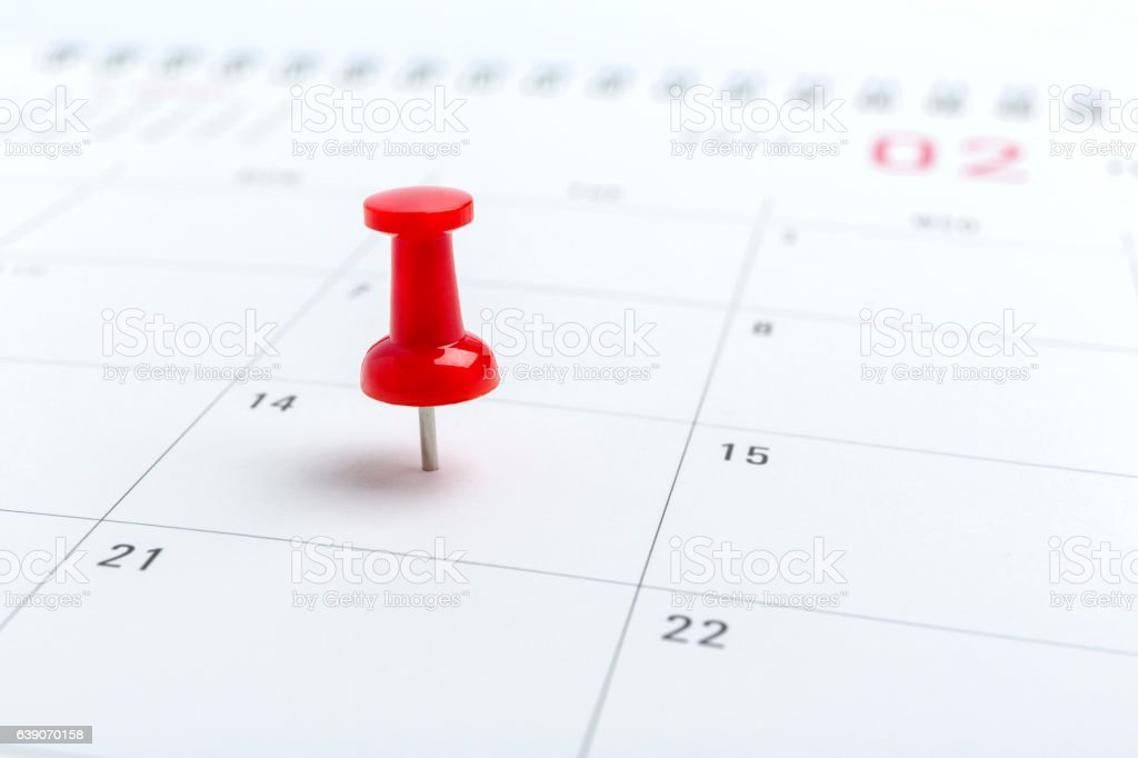 Concept image of a Calendar with red push pin. Closeup stock photo
