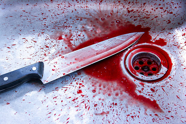 Concept image of a sharp knife with blood in sink stock photo