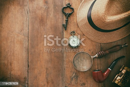 Concept image of investigation or private detective. Fedora hat, magnifing glass and vintage items over wooden table