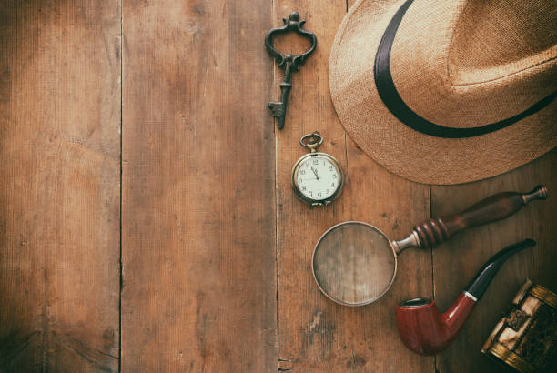 Concept image of investigation or private detective. Fedora hat, magnifing glass and vintage items over wooden table – zdjęcie