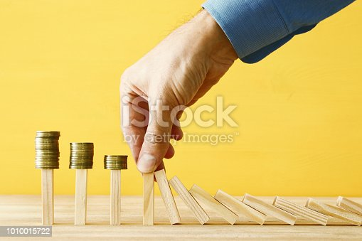 istock concept image of investing and banking. A businessman stops the domino effect from risking financial investment. 1010015722