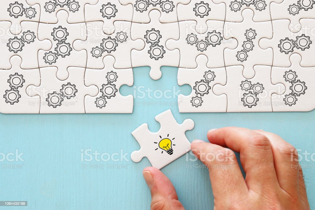 Concept image of revealing an idea, finding the right solution during creative process. Hand picking piece of puzzle with bright light bulb. royalty-free stock photo