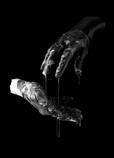 concept image of two hands covered in black and white paint touching stock photo