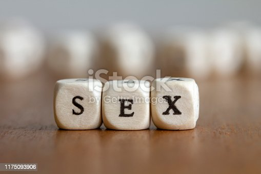 A close-up shot of the word Sex, written in wooden cubes.