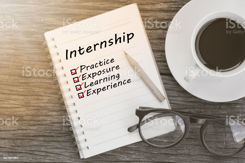 Concept Internship benefits message on notebook with glasses, pencil and coffee cup on wooden table. stock photo