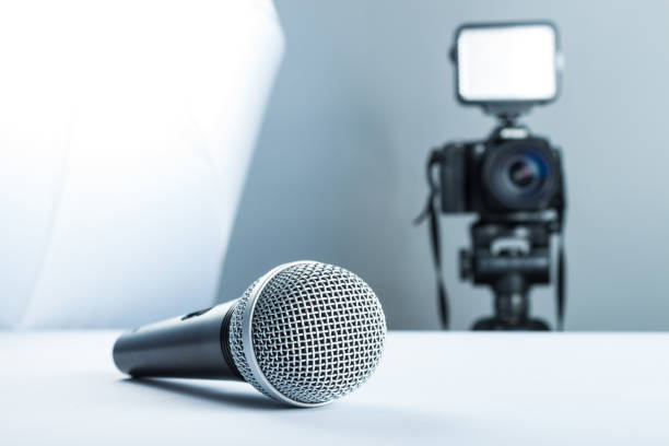 Concept interview, wireless microphone and video camera (DSLR camera) in studio on a white background. stock photo
