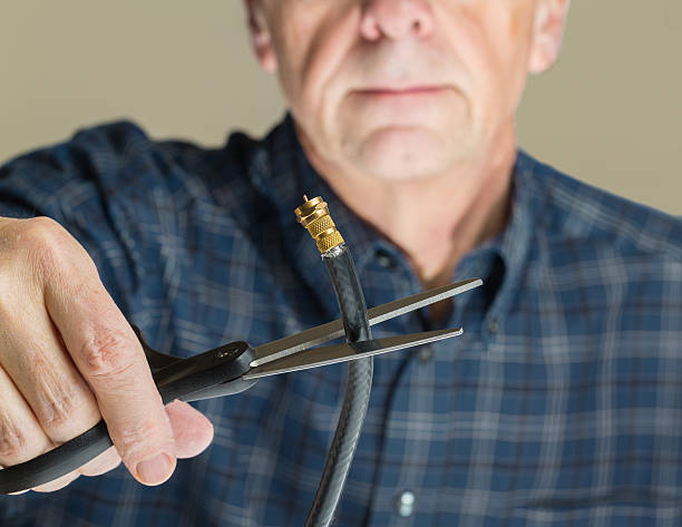 Concept isolated photo of cutting cable cord Cutting the cable connection to coax connector illustrating retired people cancelling cable TV service cable tv stock pictures, royalty-free photos & images