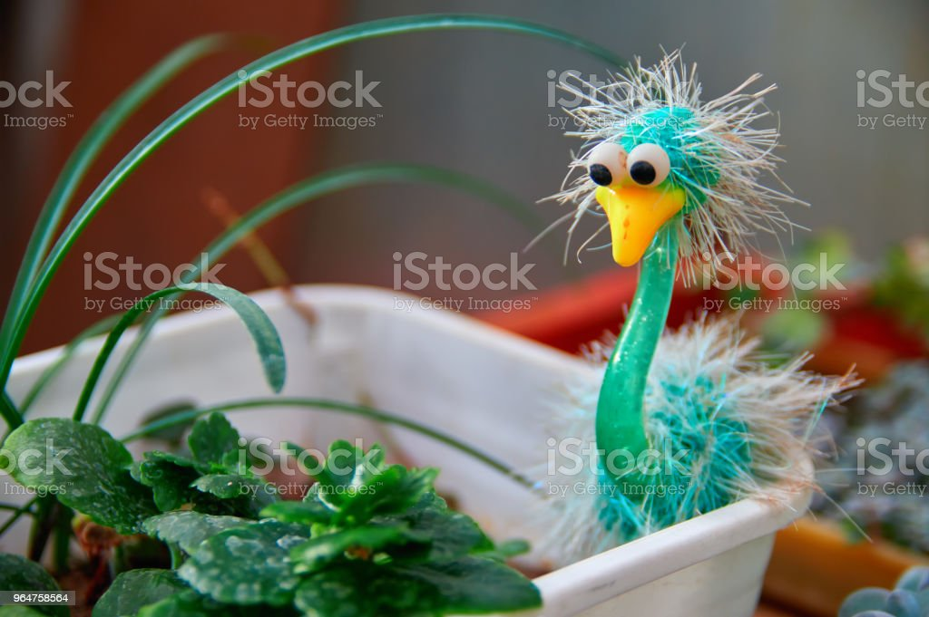 Concept lifestyle design. Green bird toy in a pot with plants in the room. royalty-free stock photo