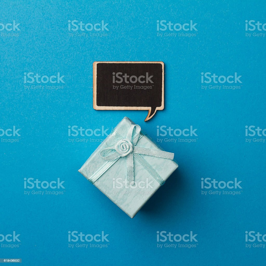 Concept little gift box with wooden speech bubble for messages stock photo