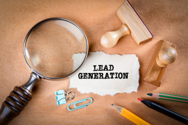 LEAD GENERATION concept. Magnifying glass, stationery and note paper stock photo