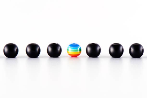 LGBT-Konzept. Viele schwarze Kugeln und einer gemalt in den Farben des Regenbogens. – Foto