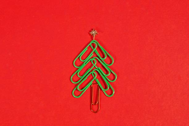 Concept merry xmas in the office. Xmas tree made of paper clips on the red background. paper clip Christmas tree. Christmas background. stock photo