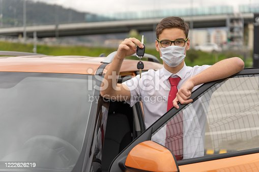 Concept of a personal driver service. Chauffeur-drive. Personal chauffeur in a protective face mask