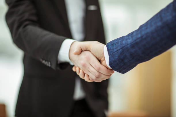 concept of a reliable partnership : a handshake of business partners closeup of handshake of business partners on the background of bright office. diplomacy stock pictures, royalty-free photos & images