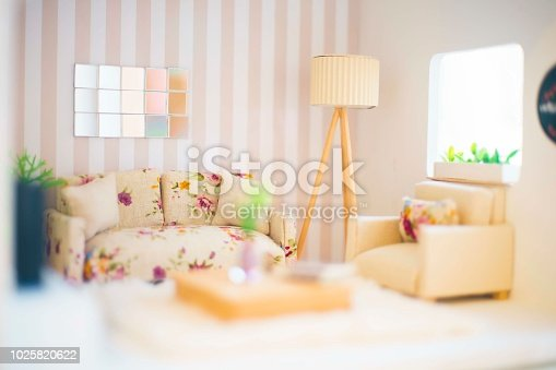 Concept of a small room with a sofa and armchair, a mirror on the wall, windows in the corner with plants and a lamp in the corner and different furniture. Small puppet house.