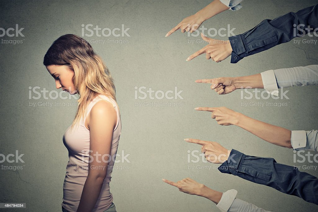 Concept of accusation guilty person girl Concept of accusation guilty person girl. Side profile sad upset woman looking down many fingers pointing at her back isolated on grey office wall background. Human face expression emotion feeling 2015 Stock Photo