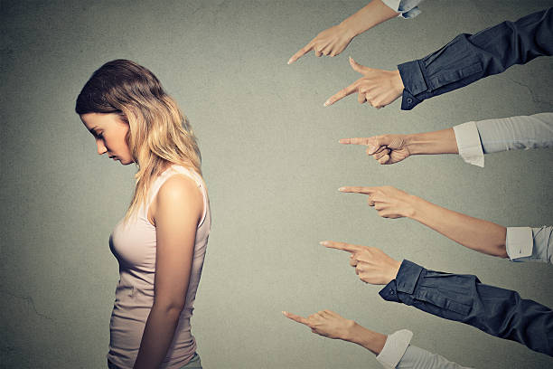 Concept of accusation guilty person girl Concept of accusation guilty person girl. Side profile sad upset woman looking down many fingers pointing at her back isolated on grey office wall background. Human face expression emotion feeling prettige verrassingen stock pictures, royalty-free photos & images