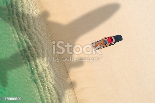 1058205304 istock photo Concept of airplane travel to exotic destination with shadow of commercial airplane flying above beautiful tropical beach. Beach holidays and travel. 1176589520