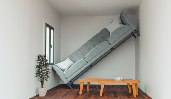 Concept of a living in a home that is not big enough for your dreams and items. Sofa cannot fit into the living room and stand up against a wall.
