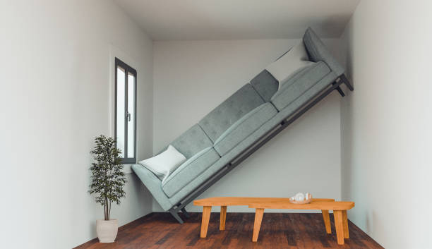 Concept of an apartment or living room that is too small to fit a sofa Concept of a living in a home that is not big enough for your dreams and items. Sofa cannot fit into the living room and stand up against a wall. narrow stock pictures, royalty-free photos & images