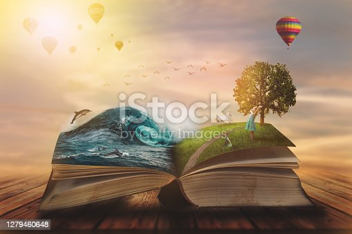 istock Concept of an open magic book; open pages with water and land and small child. Fantasy, nature or learning concept, with copy space 1279460648