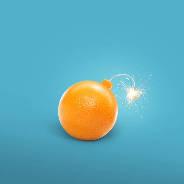 Concept of an orange bomb. Creative bomb with sparks. Juicy Orange Concept of an orange bomb. Creative bomb with sparks. Juicy Orange explosive stock pictures, royalty-free photos & images