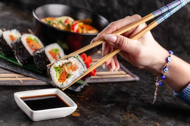 begreppet asiatiska rätter. flickan är i en kinesisk eller japansk restaurang sushi, innehar trä pinnar i händerna. dunk sushi i sojasås. olika asiatiska rätter finns på bordet - sushi bildbanksfoton och bilder