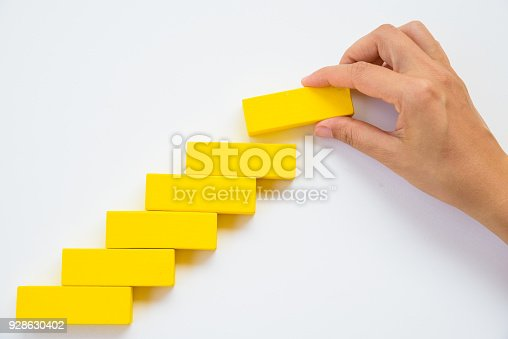 istock Concept of building success foundation. Women hand put red wooden block on yellow wooden blocks in the shape of a staircase 928630402