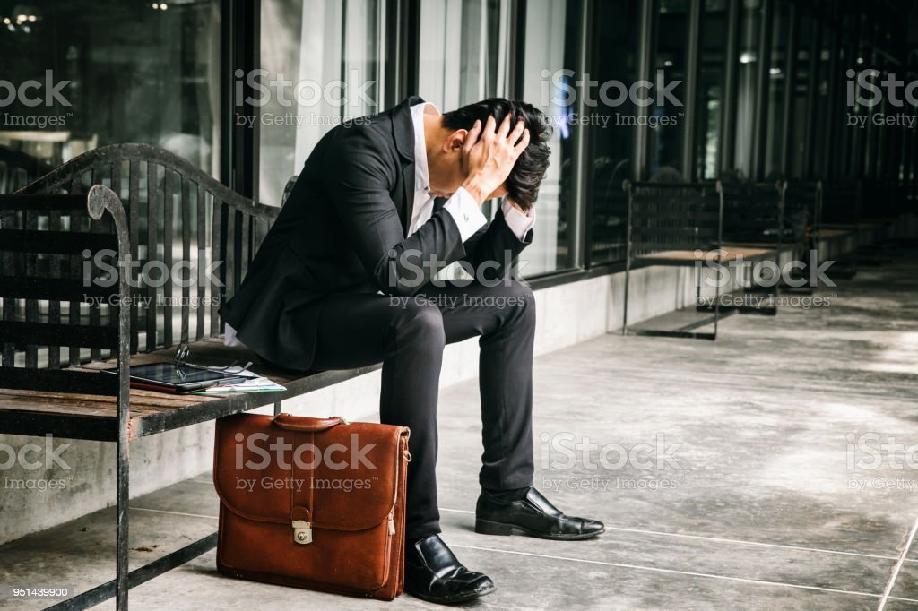 Concept of business failure and unemployment problem.An unemployed businessman sits alone in the corridor of an office. Is stressed about the future. stock photo