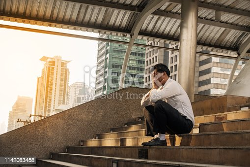 concept of business failure and unemployment problem.Exhausted Middle-aged man sitting on the stairs with hands close his face. Unemployed Businessman frustrated and desperate to find work.