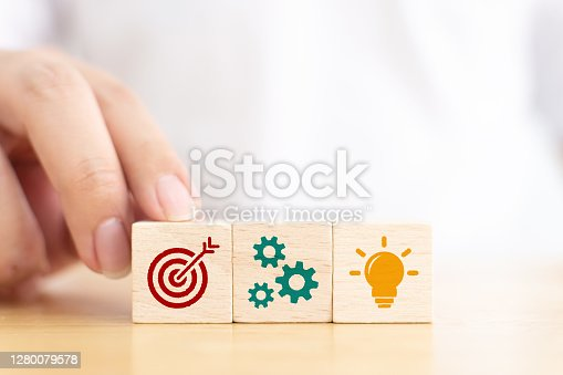 Concept of business planning strategy and action plan. Hand of male in white shirt choose wooden cube block with icon aiming goal, cog mechanism and light bulb mean idea creativity on wood table