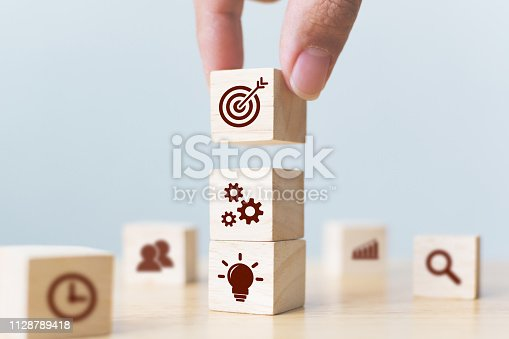 Concept of business strategy and action plan. Businessman hand putting wood cube block on top with icon