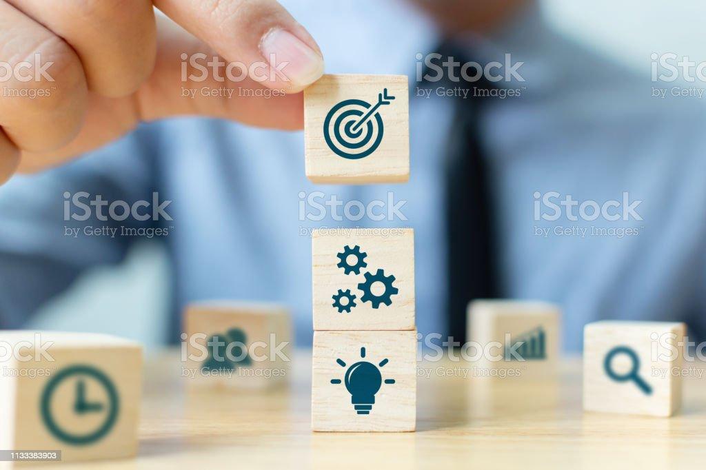 Conceito da estratégia de negócio e da planta de ação. Mão do homem de negócios que põr o bloco de madeira do cubo na parte superior - Foto de stock de Arranjo royalty-free