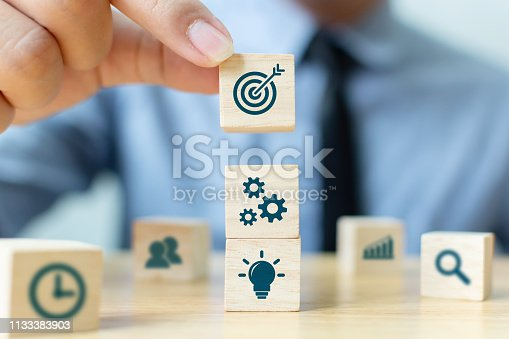 istock Concept of business strategy and action plan. Businessman hand putting wood cube block on top with icon 1133383903
