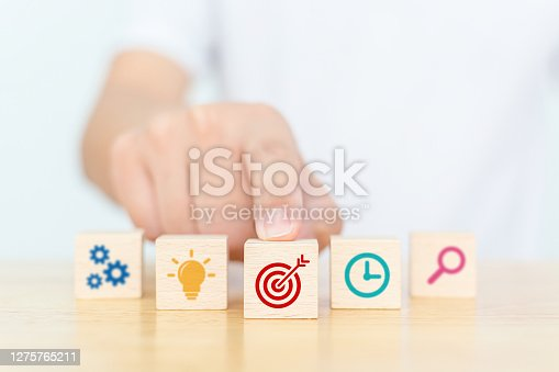 Concept of business strategy and action plan work successfully and achieve goals. Hand touching wooden cube block with icon aim, time, magnification, light bulb and cog mechanism
