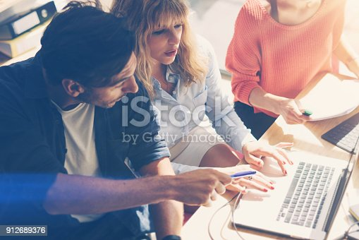912675036 istock photo Concept of business team at working process.Young professionals work with new market project. Project managers meeting.Blurred background.Horizontal.Flares. 912689376