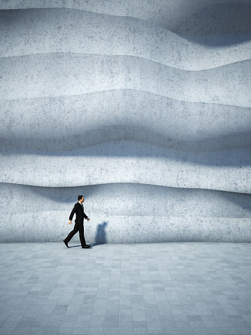 Concept of businessman walking along the abstract design wall