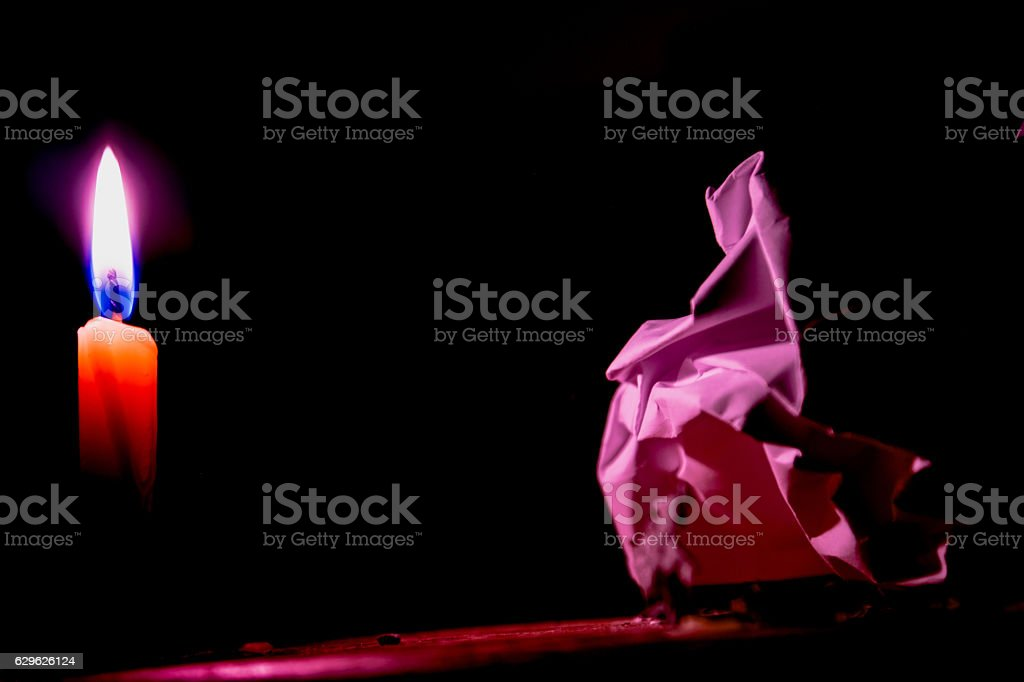 Concept of Candle flame light at night with paper. stock photo