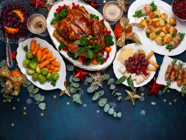 Concept of Christmas or New Year dinner with roasted chicken and various vegetables dishes. Concept of Christmas or New Year dinner with roasted chicken and various vegetables dishes. Top view. dinner stock pictures, royalty-free photos & images