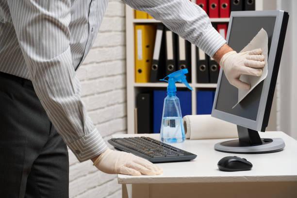 concepto de limpieza o desinfección de la oficina - un hombre de negocios limpia el lugar de trabajo, computadora, escritorio, utiliza una pistola de pulverización y servilletas de papel. Limpieza de superficies de microbios, virus y suciedad. - foto de stock
