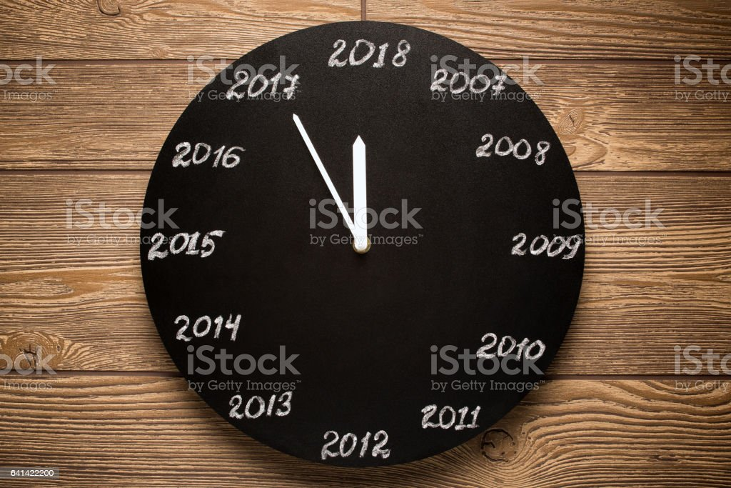 Concept of clock on the eve of 2018. Wooden background. stock photo
