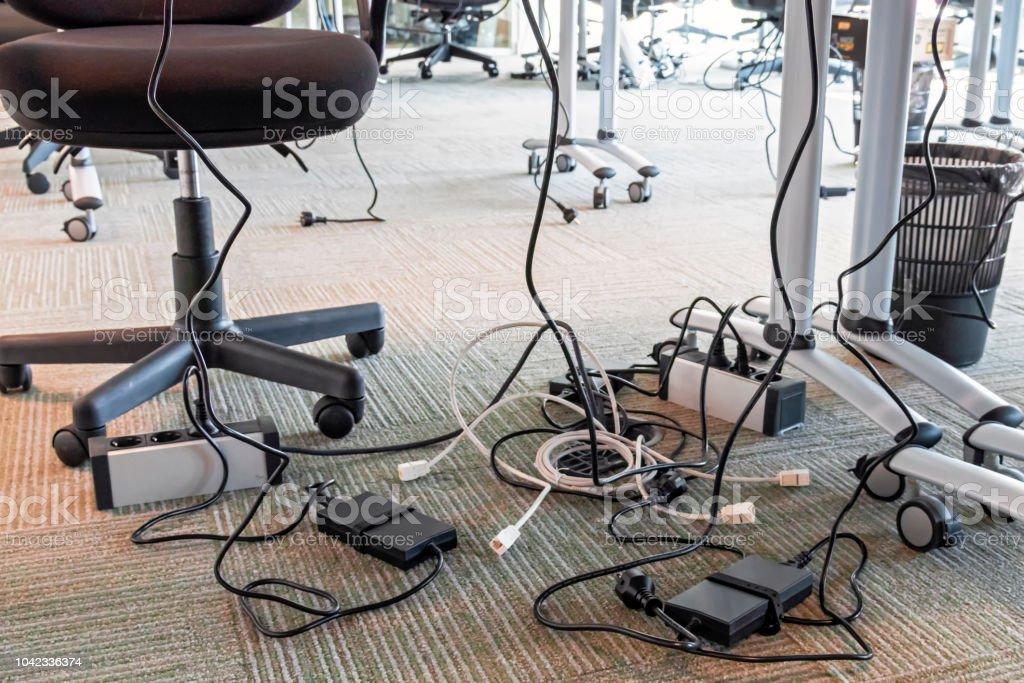 Conceito de desordem no escritório. Desenrolado e emaranhados fios elétricos debaixo da mesa. 5s-sistema de manufatura enxuta. - foto de acervo