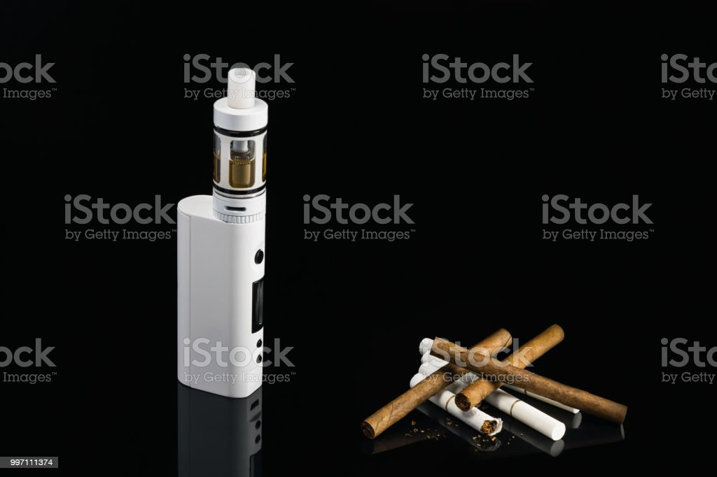concept of comparing cigarettes and vaping on a black background stock photo