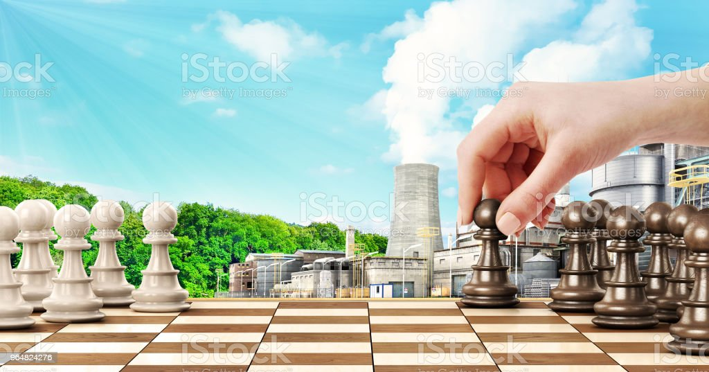 concept of confrontation. Female hand playing chess on factory and forest background royalty-free stock photo