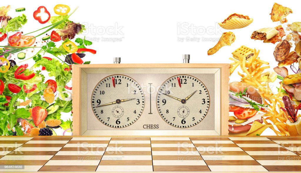 concept of confrontation. Harmful and healthy food are on the opposite sides of a chessboard on a white background. oncept of a healthy lifestyle. royalty-free stock photo
