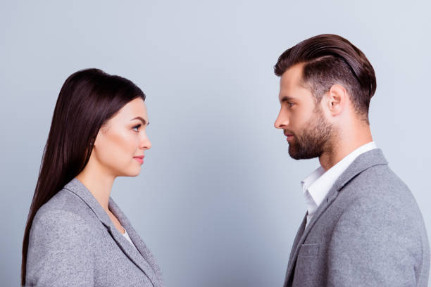 Concept of confrontation in business. Close up photo of two young serious confident people standing face-to-face to each other stock photo