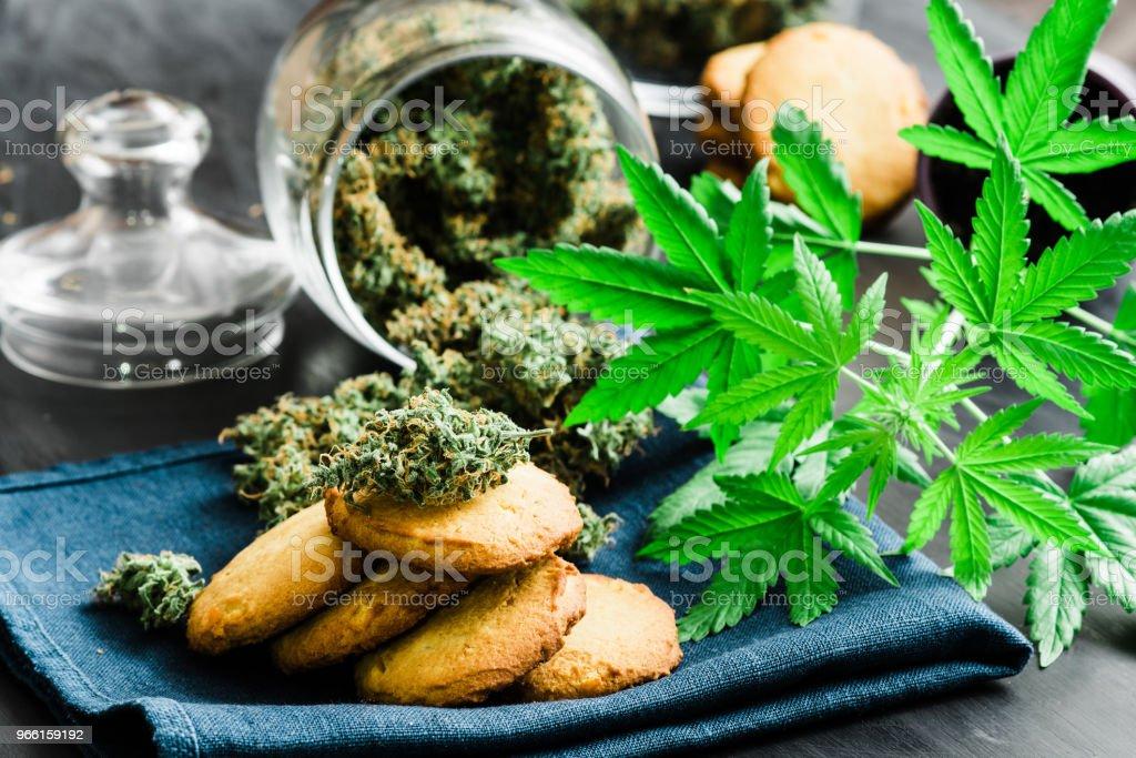 Begreppet matlagning Cookies med knoppar cannabis med cannabis herb Cookies med knoppar cannabis och marijuana på bordet. - Royaltyfri Choklad Bildbanksbilder