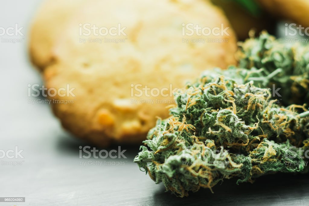 Concept of cooking with cannabis herb. Cookies with cannabis and buds of marijuana on the table. A can royalty-free stock photo