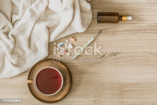 Concept of Corona Flu Virus Quarantine - Composition of Capsules and Pills, Cup of Tea, Thermometer, Blanket and Oral Drops on Wooden Background